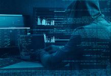 Hacker vor mehreren Bildschirmen