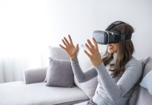 Young elegant woman sitting on sofa chair wearing virtual reality goggles looking online website and using hand moving 3D simulation screen. Enjoying new reality. Attractive young woman in VR headset